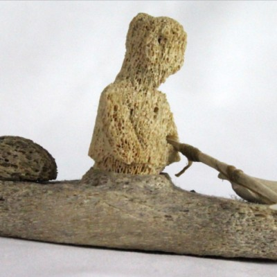 Inuit whalebone carving of hunter in kayak by William Pigalak
