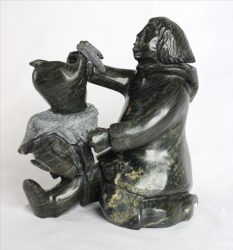 Inuit carving of man skinning rabbit by Kellipalik Qimirpik
