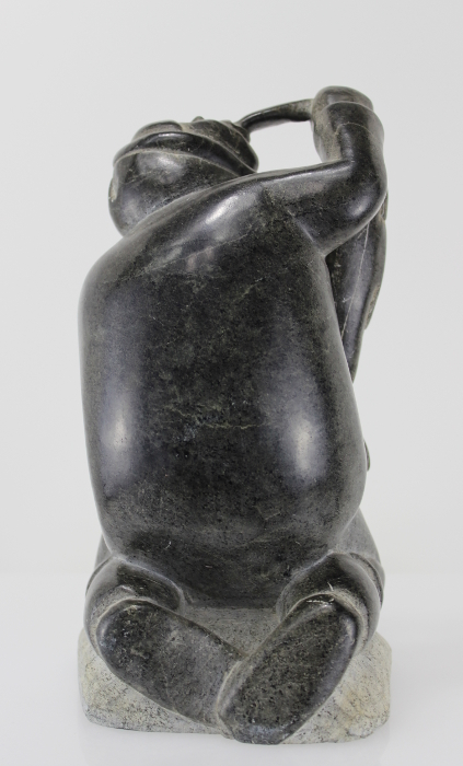 Carving of kneeling Inuk eating fish