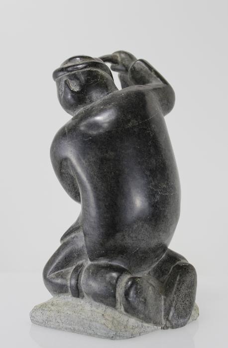 Carving of kneeling Inuk eating fish