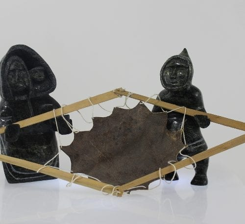 Drying skin, a three piece carving by Mosesee Pootoogook