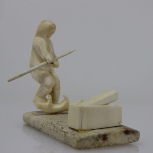 Man with spear and dog and cage by Unidentified carved in bone